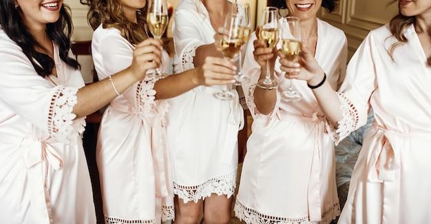 Bruid en bruidsmeisjes staan in zijden gewaden met een bril van champa Gratis Foto