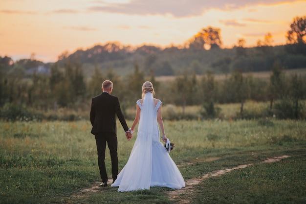 Bruid en de bruidegom hand in hand na de huwelijksceremonie in een veld bij zonsondergang Gratis Foto
