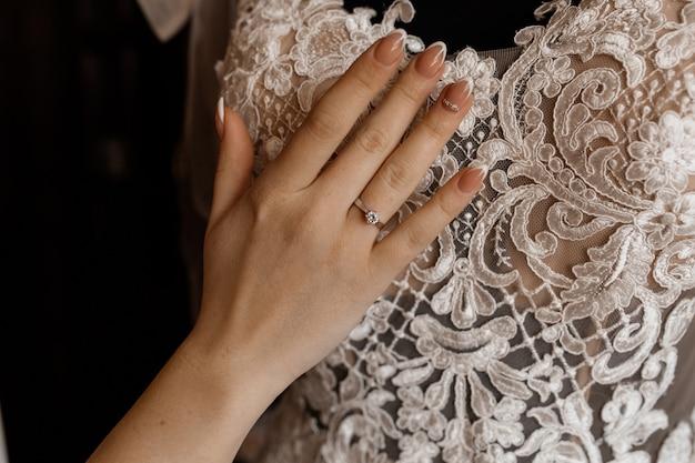 Bruid houdt haar hand op opgehangen bruidsjurk Gratis Foto