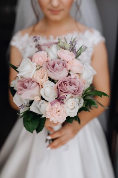 Bruid houdt het prachtige bruidsboeket met witte, paarse en roze rozen Gratis Foto