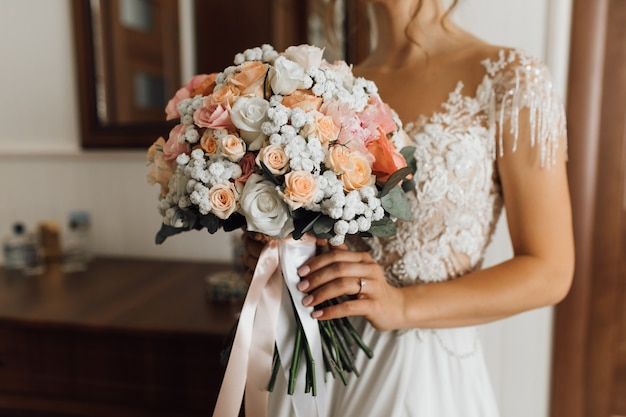 Bruid houdt het weelderige boeket met delicate bloemenkleuren Gratis Foto