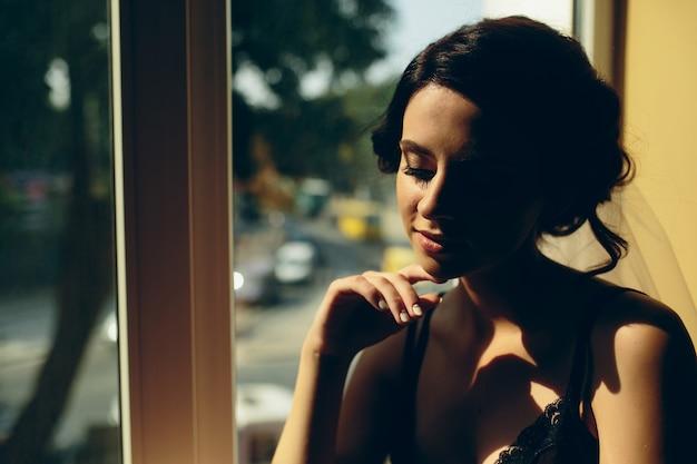Bruid in de ochtend zittend op de vensterbank Gratis Foto