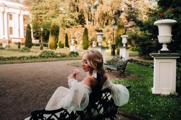 Bruid in de tuin, bruid zittend op een bankje, bruid die samenkomt, ochtendbruid, witte jurk, oorringen op. Premium Foto