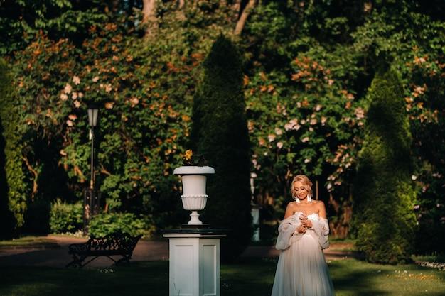 Bruid in de tuin, ochtend en bruid, bruidsprijzen, ochtendbruid, witte jurk, oorbellen dragen. Premium Foto
