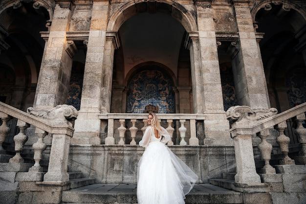 Bruid in een halve draai staat op de trappen van het oude gebouw Gratis Foto