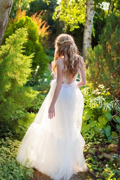 Bruid in een trouwjurk met haar rug in een groene tuin Premium Foto