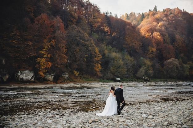 Bruid in een witte jurk en bruidegom gaan naar de rivier rotsen en hand in hand Premium Foto