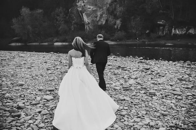 Bruid in een witte jurk en bruidegom gaan naar de rivier stenen Premium Foto