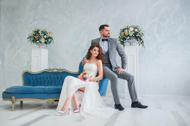 Bruid in mooie jurk en bruidegom in grijs pak zittend op de bank binnenshuis. trendy trouwstijl Premium Foto