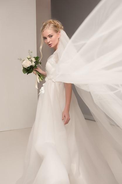 Bruid in mooie jurk permanent binnenshuis in witte studio interieur zoals thuis. trendy bruiloft stijl schot. jong aantrekkelijk kaukasisch model zoals bruid het tedere kijken. Gratis Foto