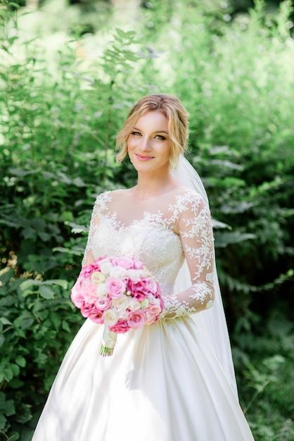Jurk Bruiloft Lange Mouw.Bruid In Stijlvolle Jurk Met Lange Mouwen Houdt Roze Bruiloft Boeket