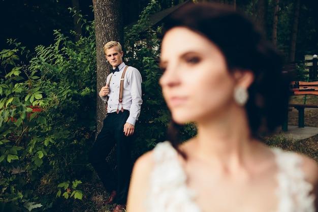 Bruid kijkt ergens op de achtergrond is de bruidegom Gratis Foto