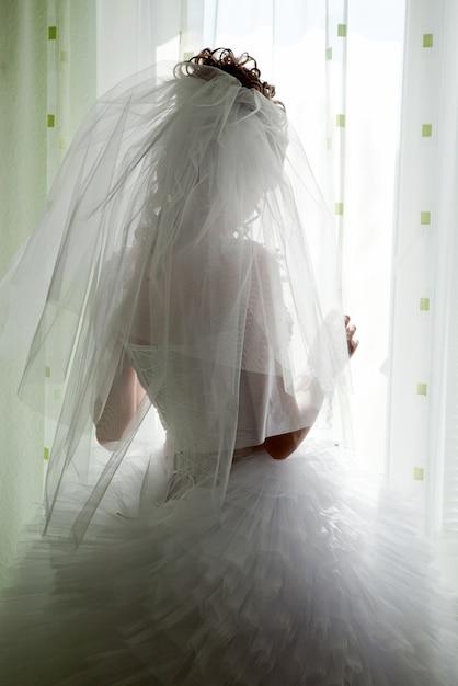 Bruid kijkt uit het raam, trouwdag Premium Foto