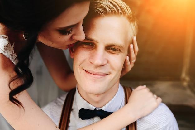Bruid leunt op de bruidegom en omhelst hem teder Gratis Foto