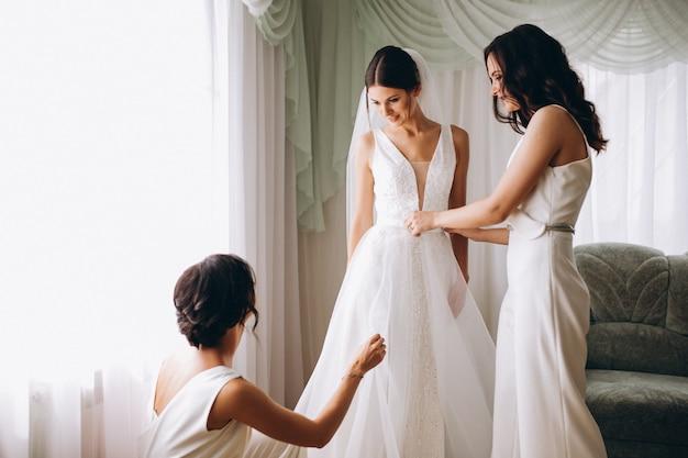 Bruid met bruidsmeisjes die voor huwelijk voorbereidingen treffen Gratis Foto
