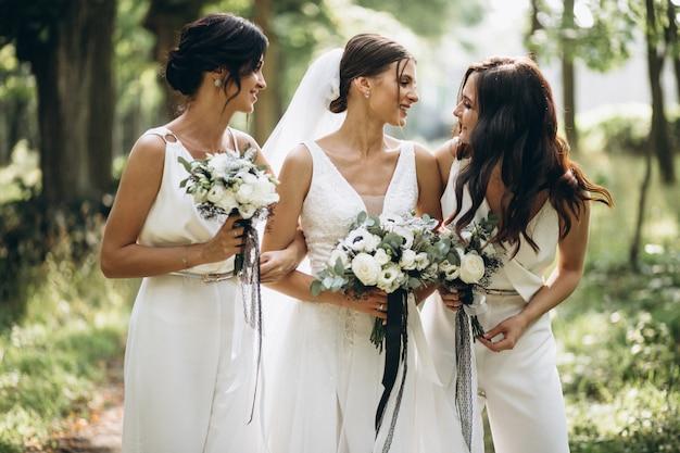 Bruid met haar bruidsmeisjes in het bos Gratis Foto