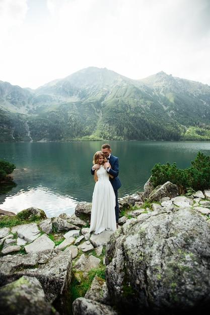 Bruid met mooie witte jurk en bruid met uitzicht op prachtige groene bergen en meer met blauw water Premium Foto