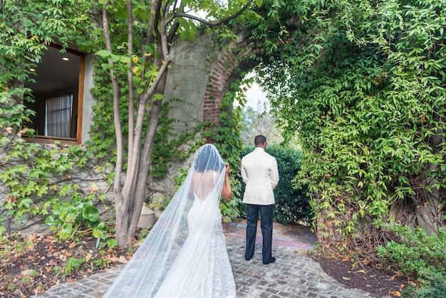 Bruid nadert de bruidegom die zich voor een natuurlijke boog bevindt Gratis Foto