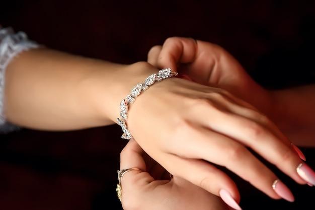 Bruid overhandigt mooie decoratie op de arm, armband. Premium Foto
