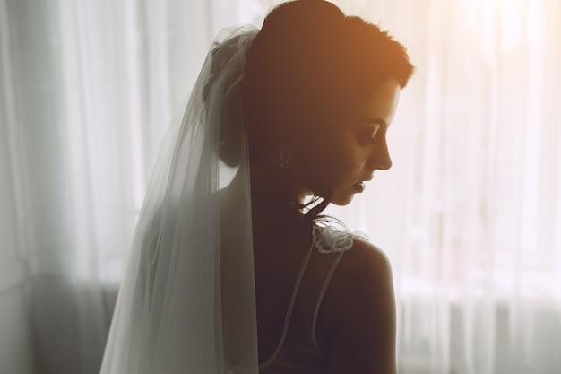 Bruid poseren in een groot raam op de camera Gratis Foto