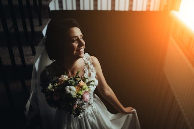 Bruid poseren op de trap naar de kamer Gratis Foto