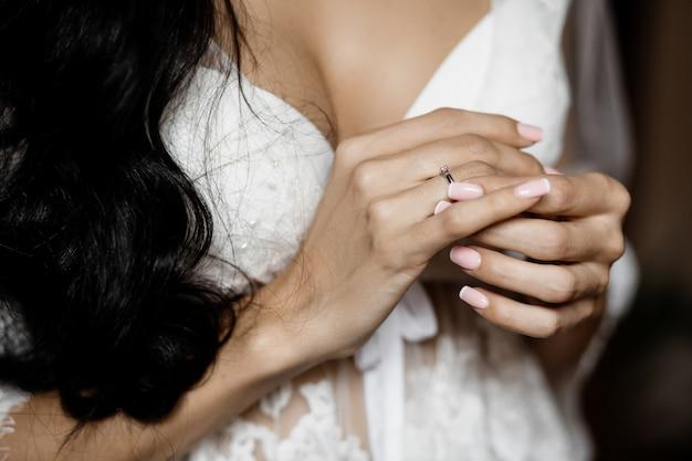 Bruid toont prachtige manicure en minimalistische verlovingsring Gratis Foto