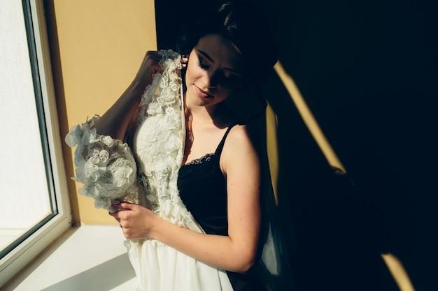 Bruid zittend op een vensterbank en houdt trouwjurk Gratis Foto