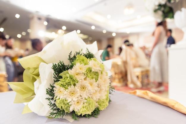 Bruidbloem op het onduidelijke beeldachtergrond van de huwelijkspartij Premium Foto