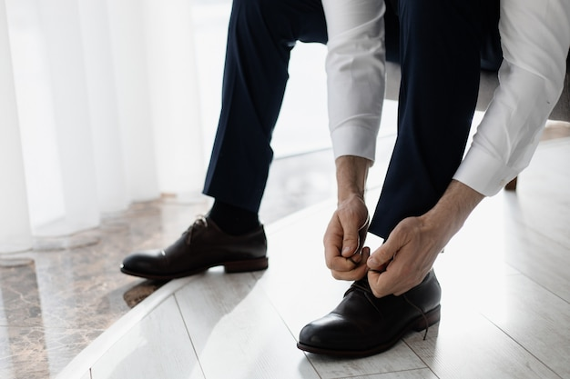 Bruidegom bindt veters aan zijn schoenen Gratis Foto