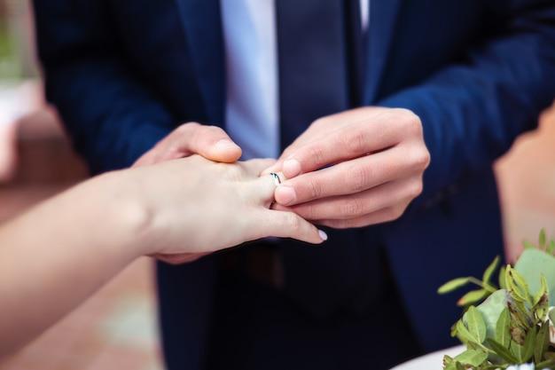 Bruidegom die trouwring op bruidvinger zet Premium Foto