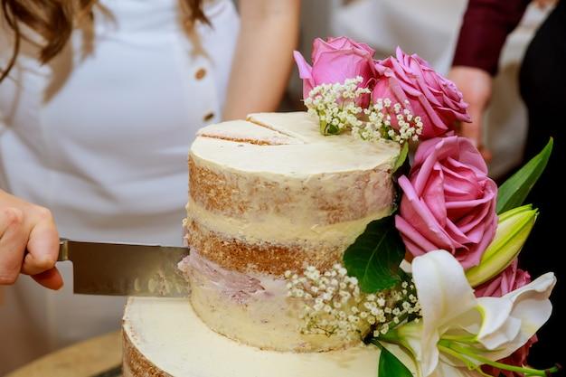 Bruidegom en bruid in witte jurk gesneden laag naakte bruidstaart, versierd met verse bloemen Premium Foto