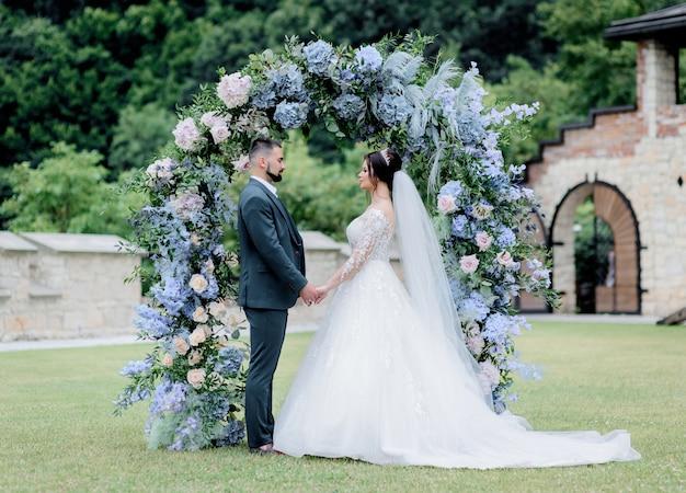 Bruidegom en bruid staan samen voor de versierde boog met blauwe hortensia, hand in hand, huwelijksceremonie, huwelijksgeloften Gratis Foto