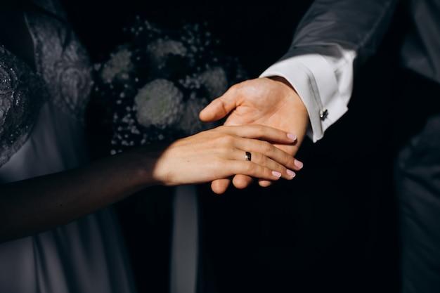 Bruidegom houdt de hand van de bruid zacht in zijn arm Gratis Foto