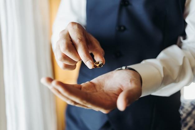 Bruidegom houdt trouwring staande voor het raam in een hotel r Gratis Foto