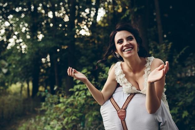 Bruidegom houdt zijn bruid ergens in de natuur in zijn armen Gratis Foto