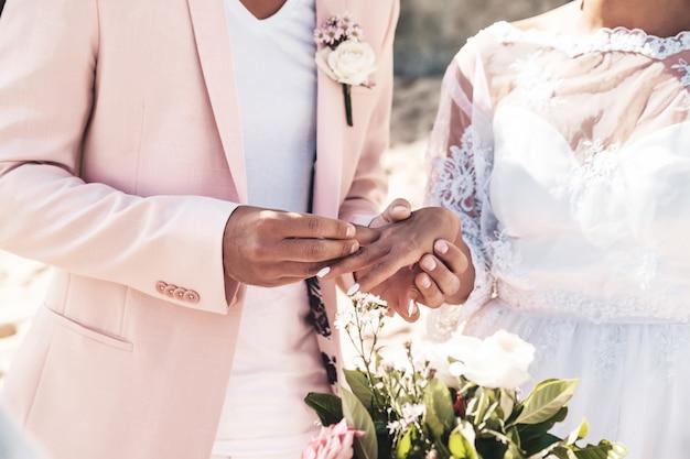 Bruidegom in roze jas draagt ring aan de vinger van de bruid op het strand Gratis Foto