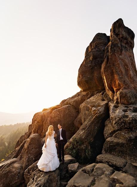 Bruidegom kijkt naar zijn vrouw terwijl hij op de hoge enorme rots staat Premium Foto