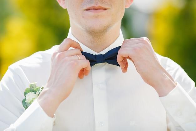 Bruidegom lost donkerblauwe vlinderdas op wit overhemd Premium Foto