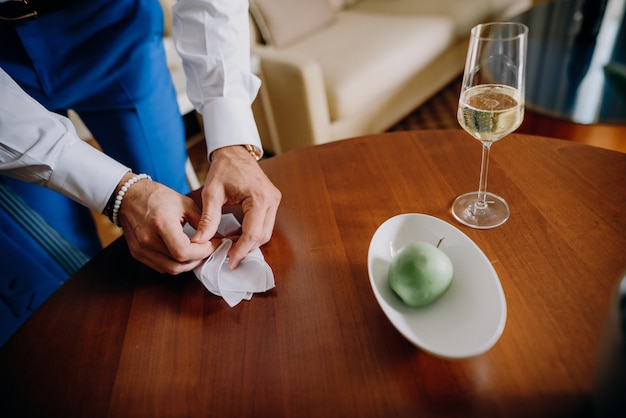 Bruidegom neemt een servet van een houten tafel Gratis Foto