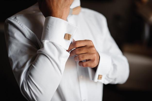 Bruidegom ochtend voorbereiding. bruidegom aankleden in een trouwjurk met houten strikje Premium Foto
