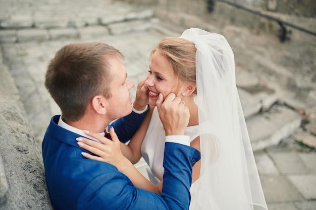 Bruidegom raakt de wangen van de bruid aan Premium Foto