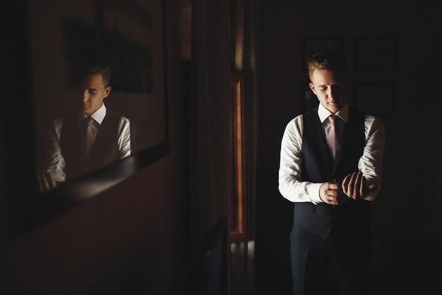 Bruidegom repareert knopen boven zijn boeien voor een raam in een klein italiaans huis Premium Foto