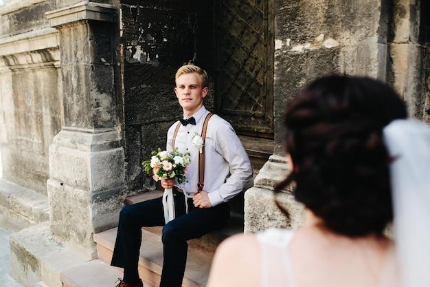 Bruidegom zittend op de stenen trap en poseert voor de camera Gratis Foto