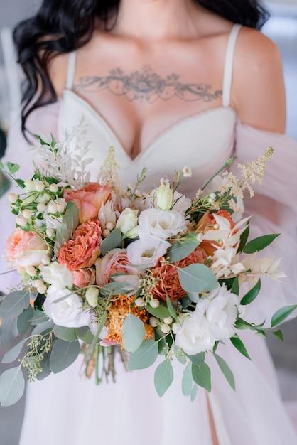 Bruidsboeket gemaakt van eustoma en eucalyptus, bruidsjurk met open decolleté en tatoeage op de borsten Gratis Foto