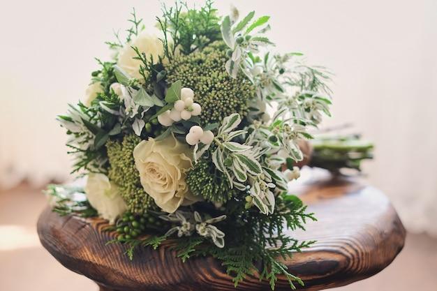 Bruidsboeket. huwelijk. huwelijksboeket van witte en groene bloemen staat op een stoel Premium Foto