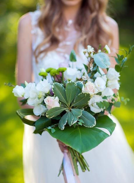 Bruidsboeket in de handen van een jong meisje Premium Foto