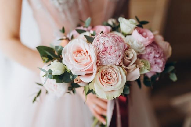 Bruidsboeket met pioenrozen, fresia en andere bloemen in handen van vrouwen. lichte en lila lentekleur. ochtend in de kamer Premium Foto
