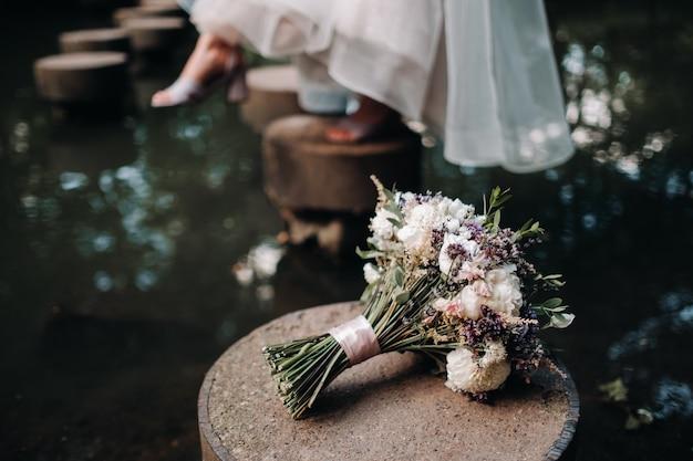 Bruidsboeket met rozen op tafel en een corsages Premium Foto