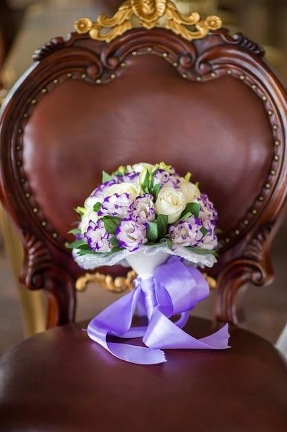 Bruidsboeket van verse bloemen op houten stoel Premium Foto