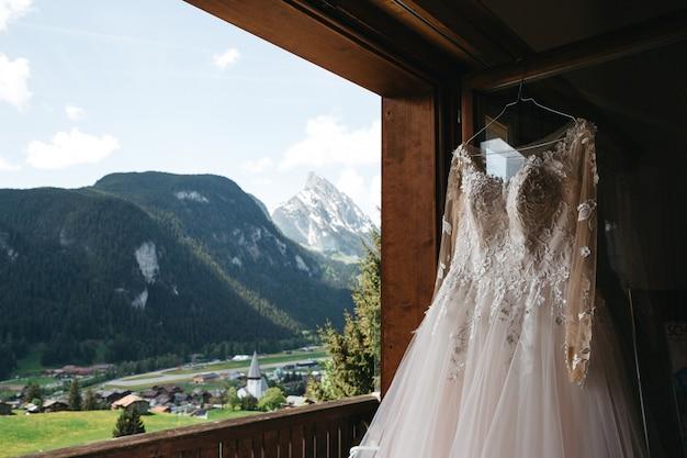 Bruidsjurk hangt aan een hanger aan een raam met uitzicht op de bergen Gratis Foto